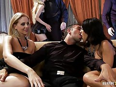 A blonde and a dark brown are rubbing a guy's crotch whilst sitting on a couch. They pull out his cock and begin to engulf it, every awaiting her turn. Another dick enters the scene and the dark brown goes to blow it.