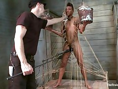 Nikki is all tied up and standing on her legs. Filled with clothespins and strings, this babe has to be careful and not to drop the two buckets she`s holding, while a large vibrator makes sensations on her soaked cunt. This babe gets all whipped for being such a bad ebon girl. Her executor will take very nice care of her!